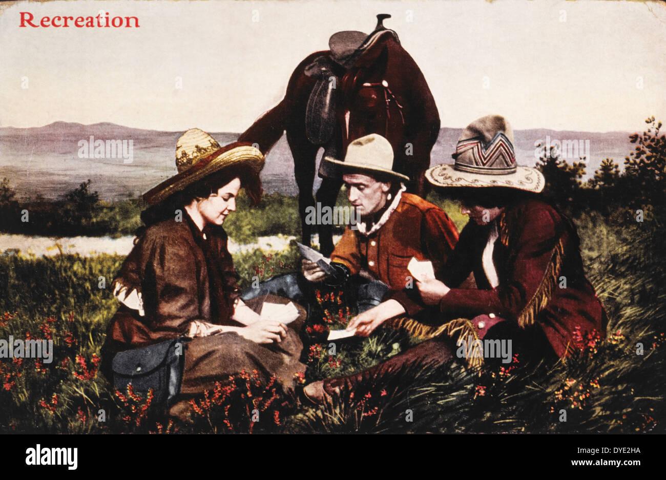 Dos vaqueros y una mujer jugando a las cartas durante un descanso en el camino, al oeste, EE.UU., circa 1909 Foto de stock