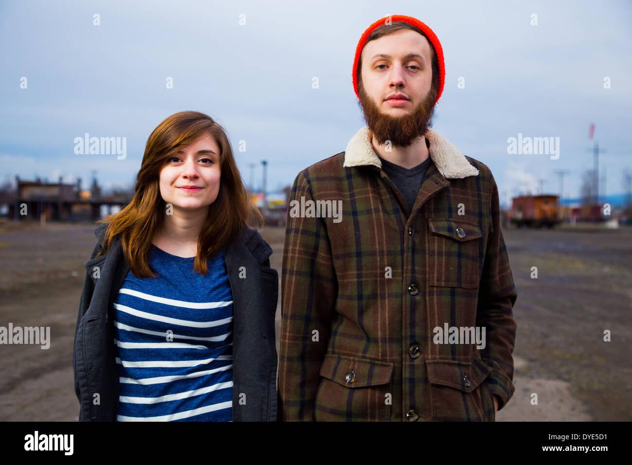 Modernos, hipster par en un patio de trenes abandonados al atardecer en este retrato de estilo de moda. Imagen De Stock