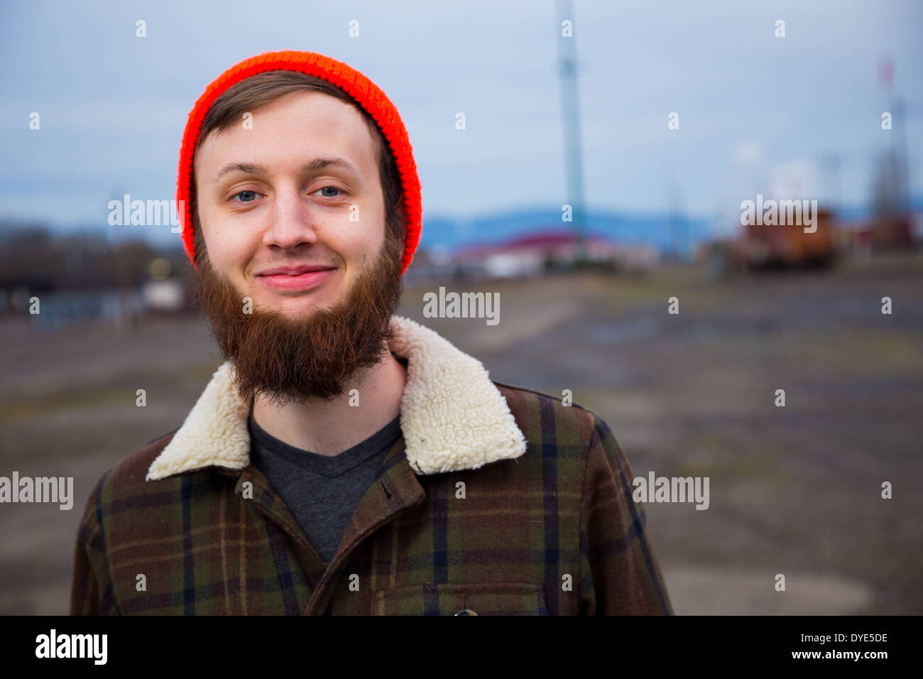 Modernos, hipster Guy en un patio de trenes abandonados al atardecer en este retrato de estilo de moda. Imagen De Stock