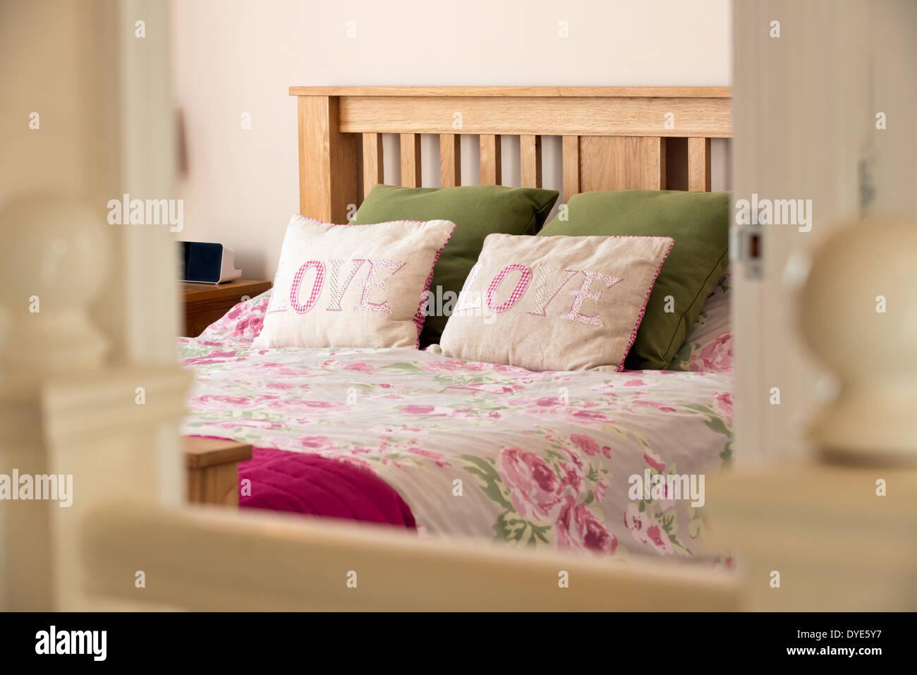 Una imagen de estilo de vida de una cama en un dormitorio acogedor con almohadas bordadas con la palabra amor a Foto de stock