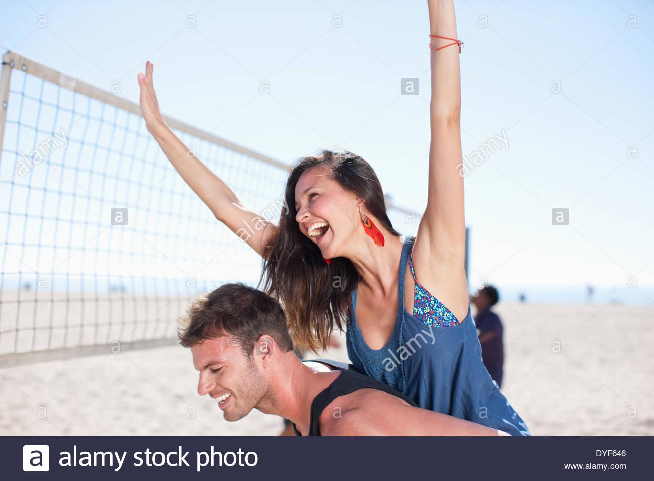 El hombre lleva novia piggyback en la playa Imagen De Stock