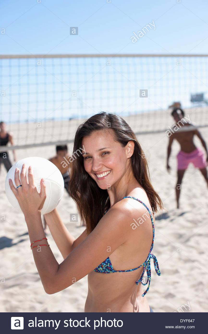 Mujer jugando voleibol de playa con amigos Imagen De Stock