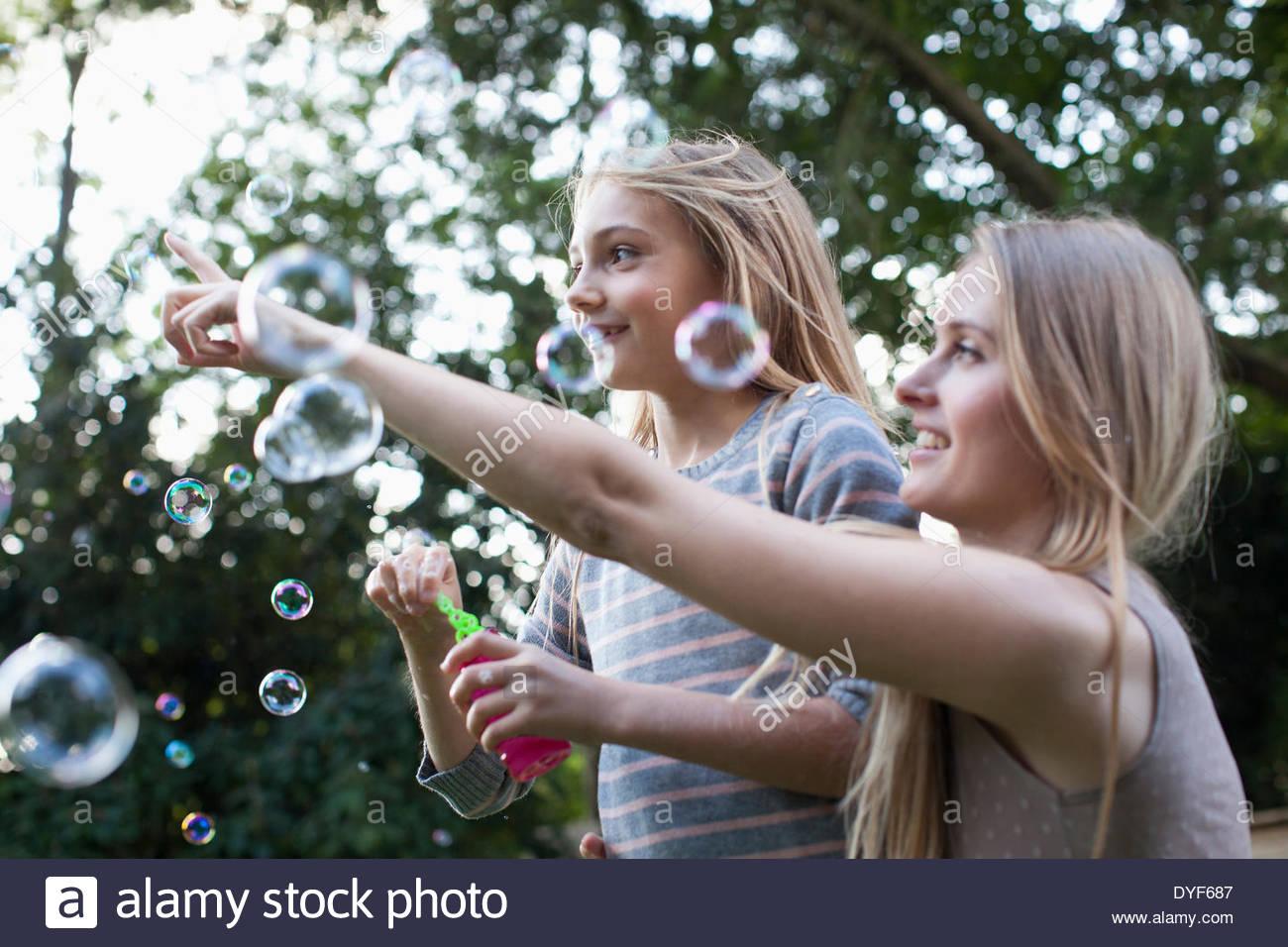 Madre e hija soplando burbujas debajo de árbol Imagen De Stock