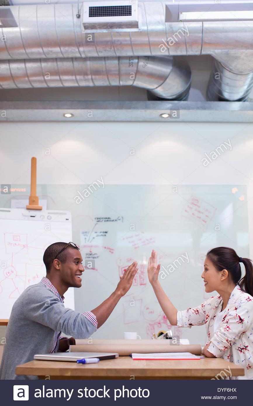 La gente de negocios de alta fiving en Office Imagen De Stock