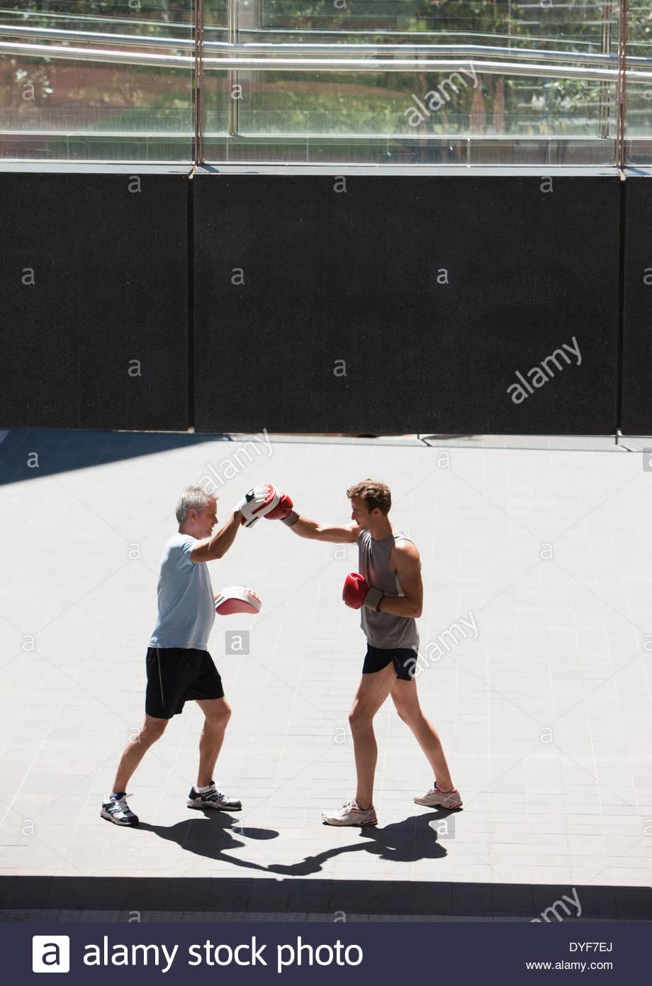 Boxer con el entrenador de formación al aire libre Imagen De Stock