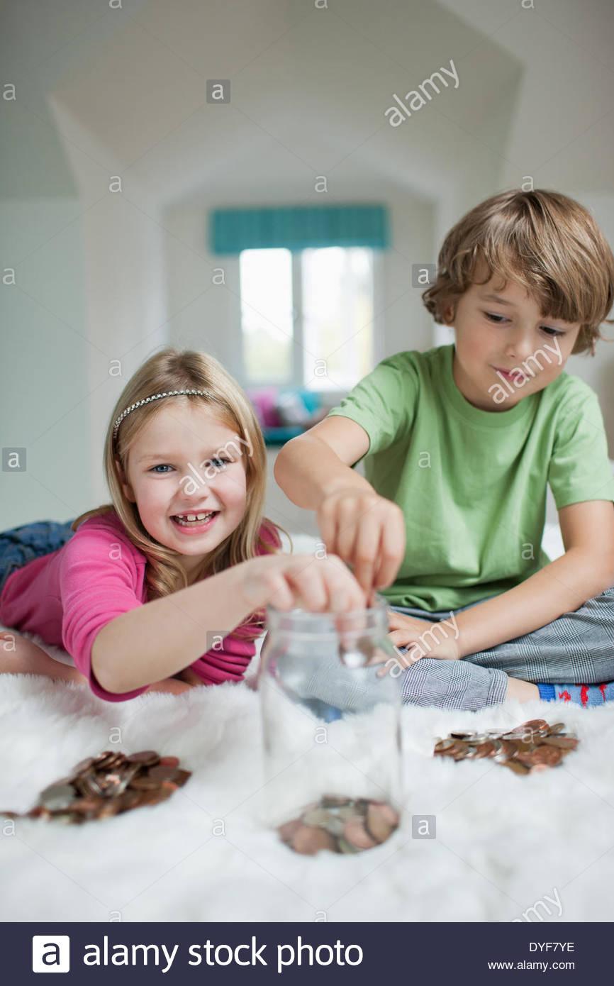 Hermano, hermana jugando contando dinero en dormitorio Imagen De Stock