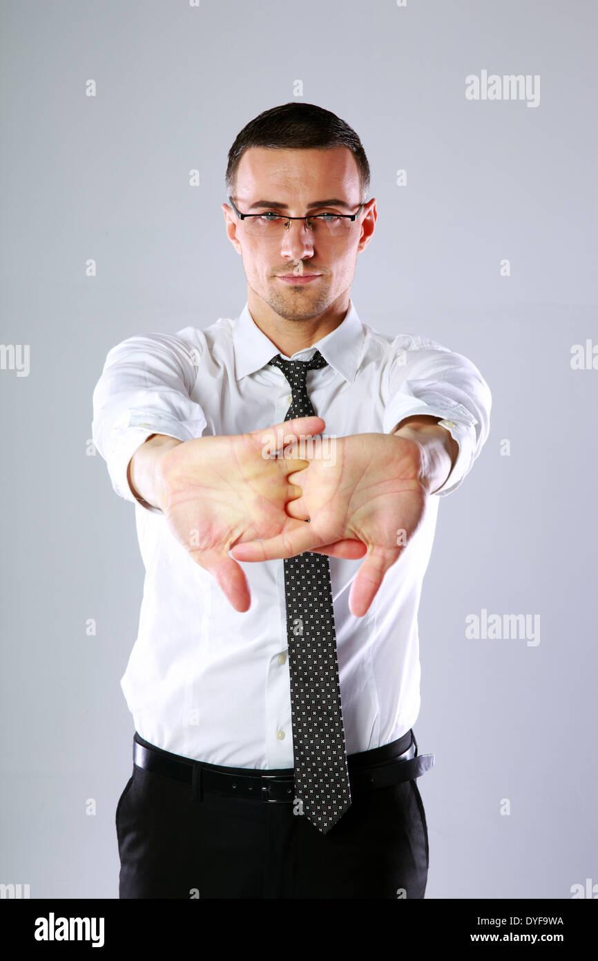 Empresario estiramientos después de un agotador trabajo sobre fondo gris Imagen De Stock