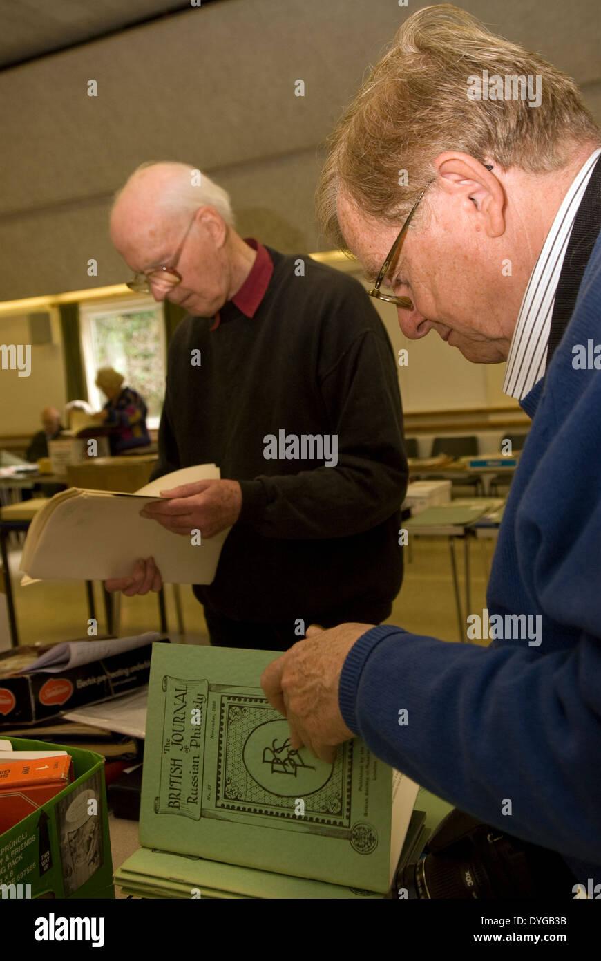 Los ancianos que asisten a una subasta de sello y examina los elementos para ser vendidos, petersfield, Hampshire, Foto de stock