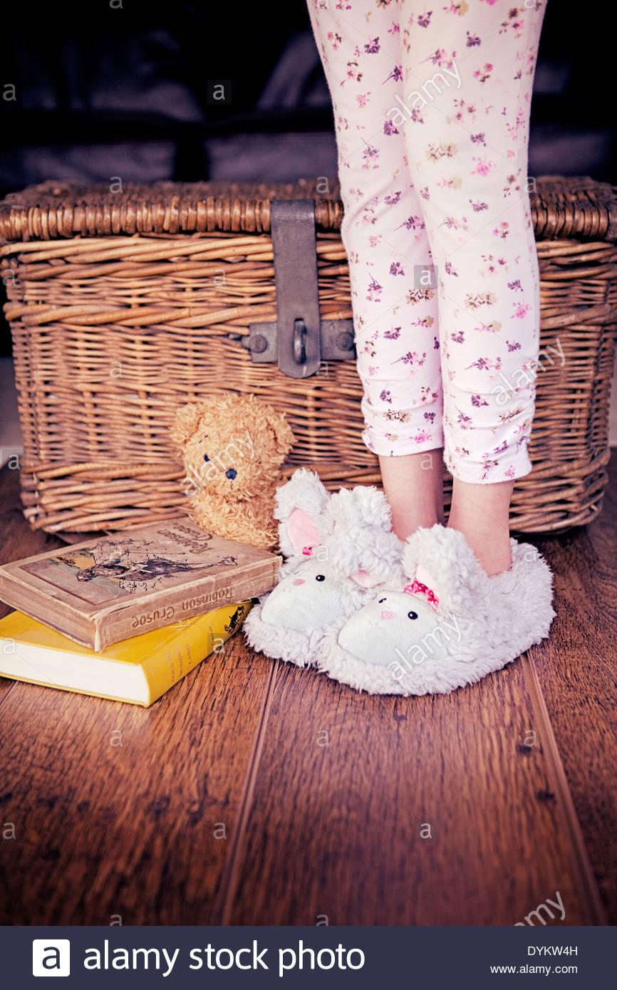 Imagen de un niño lindo pijama de piernas y mullidas zapatillas con un par de libros y un osito de peluche junto a ella en un piso de madera. Imagen De Stock