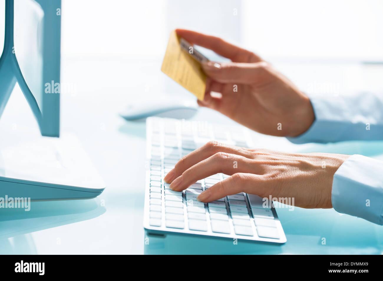 Mujer de compras en internet mediante tarjeta de crédito y computadora Imagen De Stock
