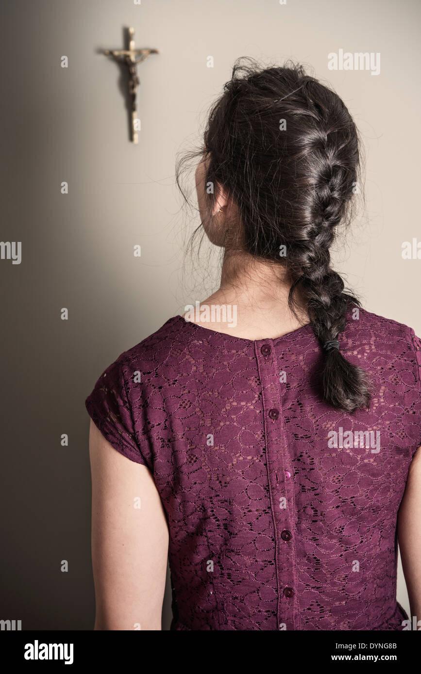 Vista posterior de la mujer mirando al crucifijo colgado en la pared Imagen De Stock