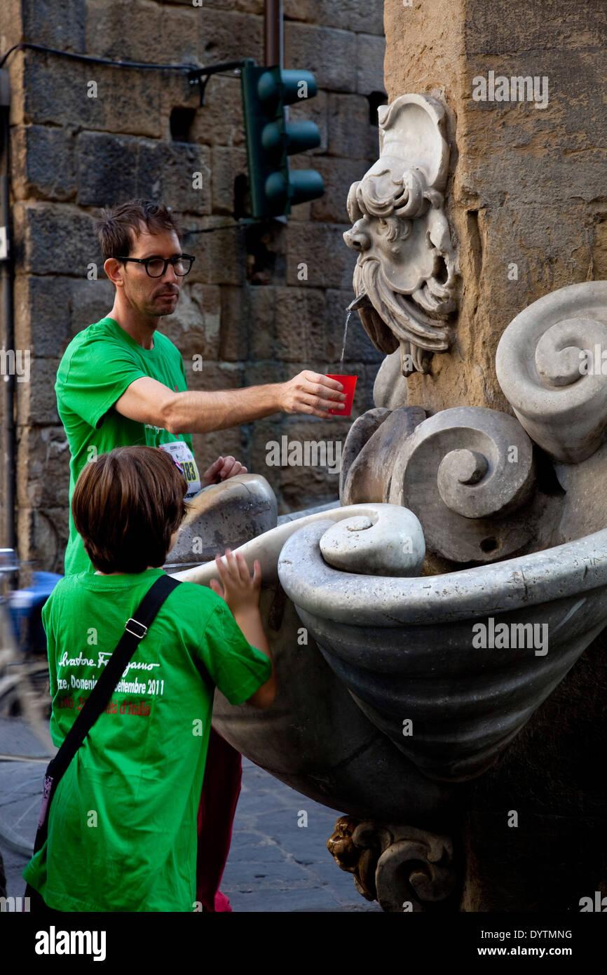 Hombre con niño sosteniendo taza coger agua de la fuente, Florencia, Italia. Imagen De Stock