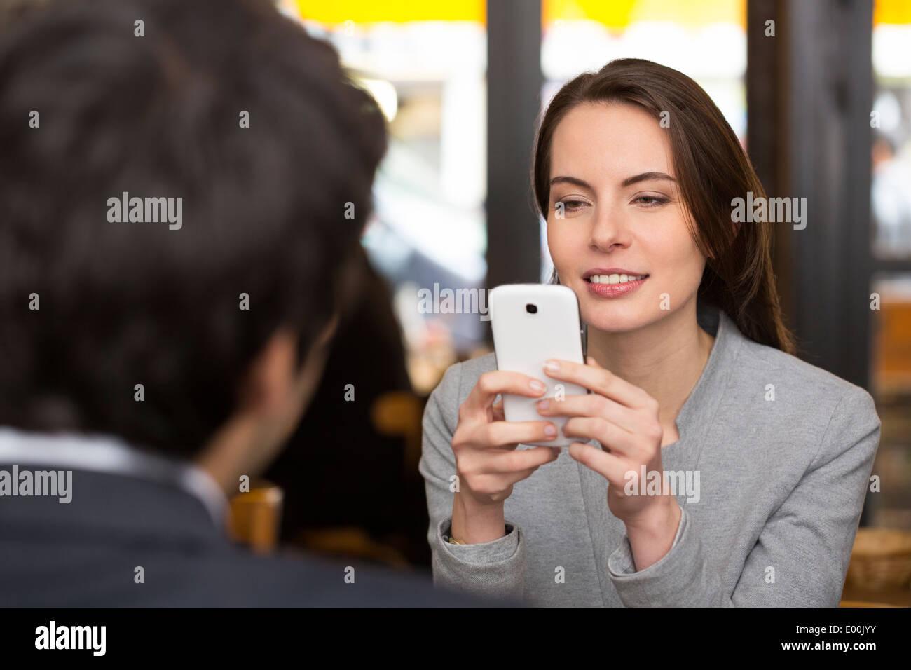 Macho hembra alegre bar cena smartphone sms surf web Imagen De Stock