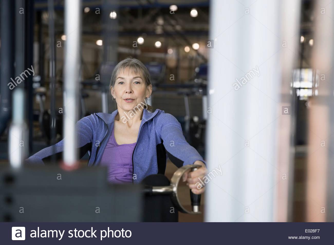 Mujer con máquina de ejercicio en el gimnasio Imagen De Stock