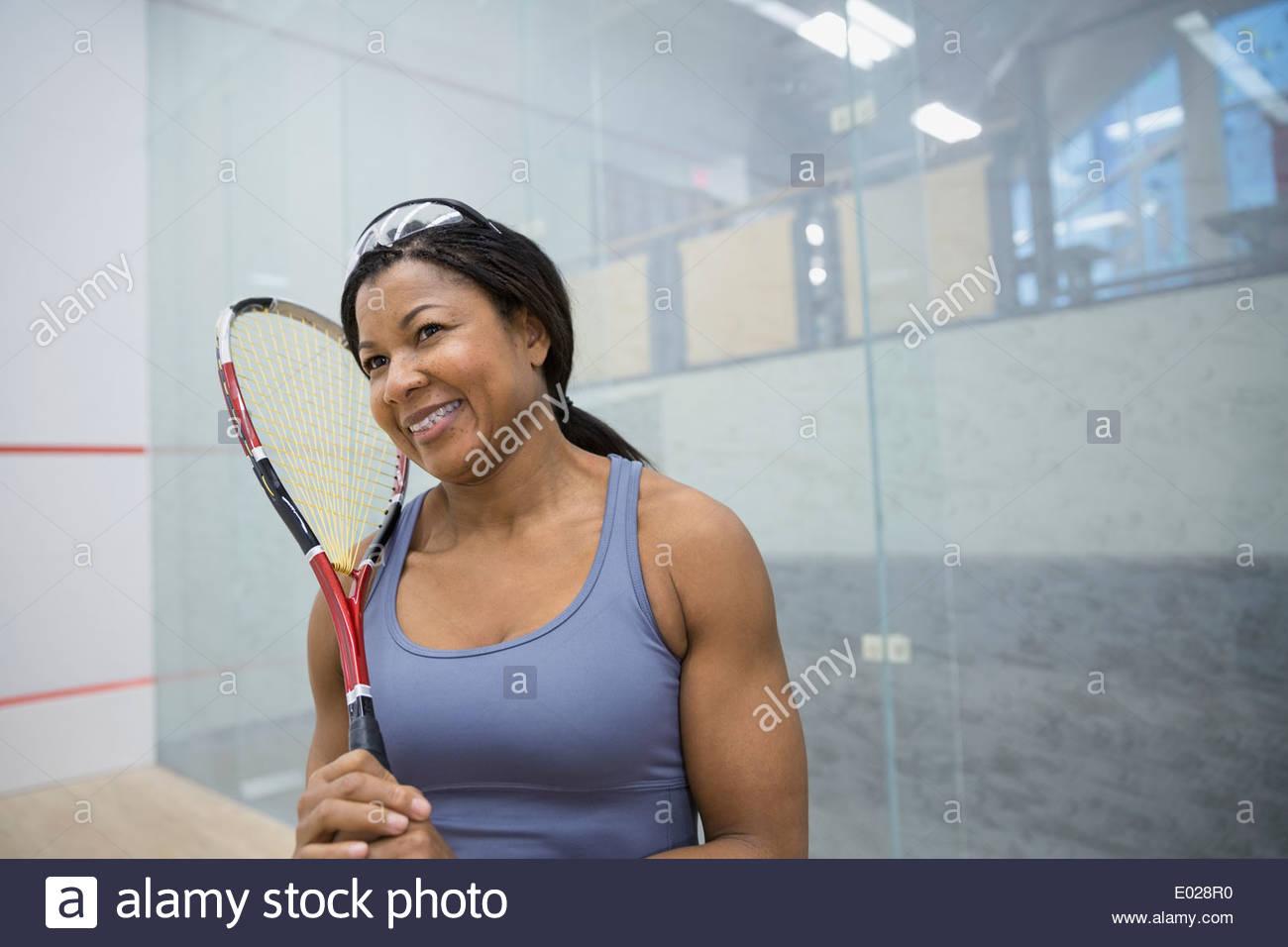 Mujer sonriente Celebración raquetas de squash Imagen De Stock