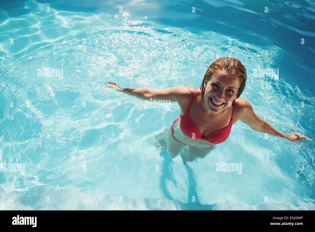 Feliz joven relajándose en la piscina. Sonriente joven mujer vistiendo trajes de baño en la piscina de pie mirando Foto de stock