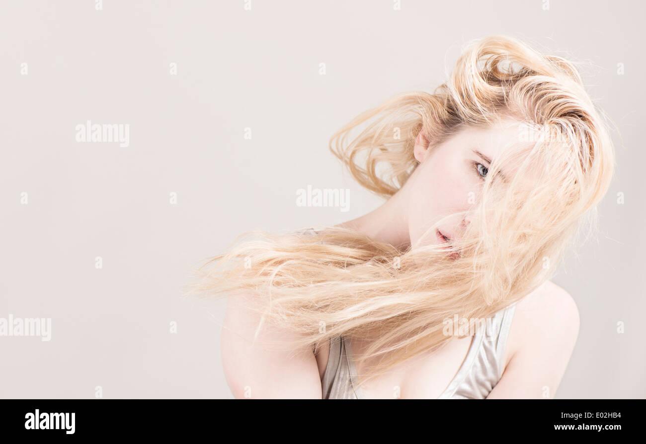 Hermosa joven mujer rubia con cabello largo delante de su rostro. Mostrar expresión de enfriar la actitud y personalidad. Imagen De Stock