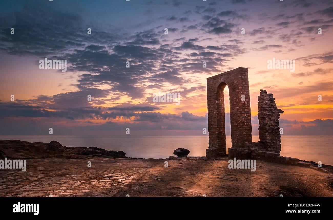 La puesta de sol sobre el mar y la costa rocosa con ruinas antiguas y puerta a África en Mahdia, Túnez Imagen De Stock