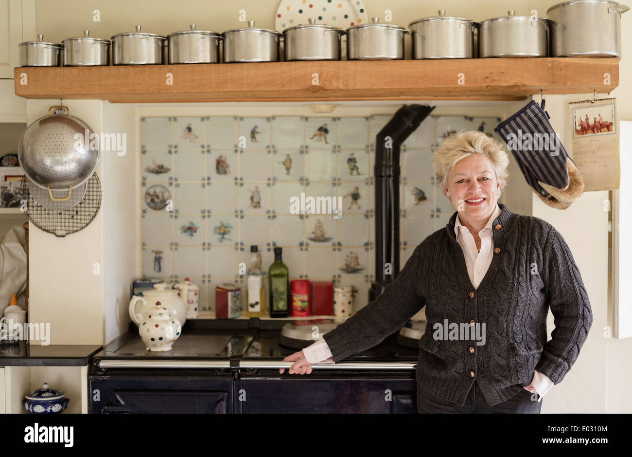 Una mujer de pie con su espalda a una cocina en su cocina Foto ...