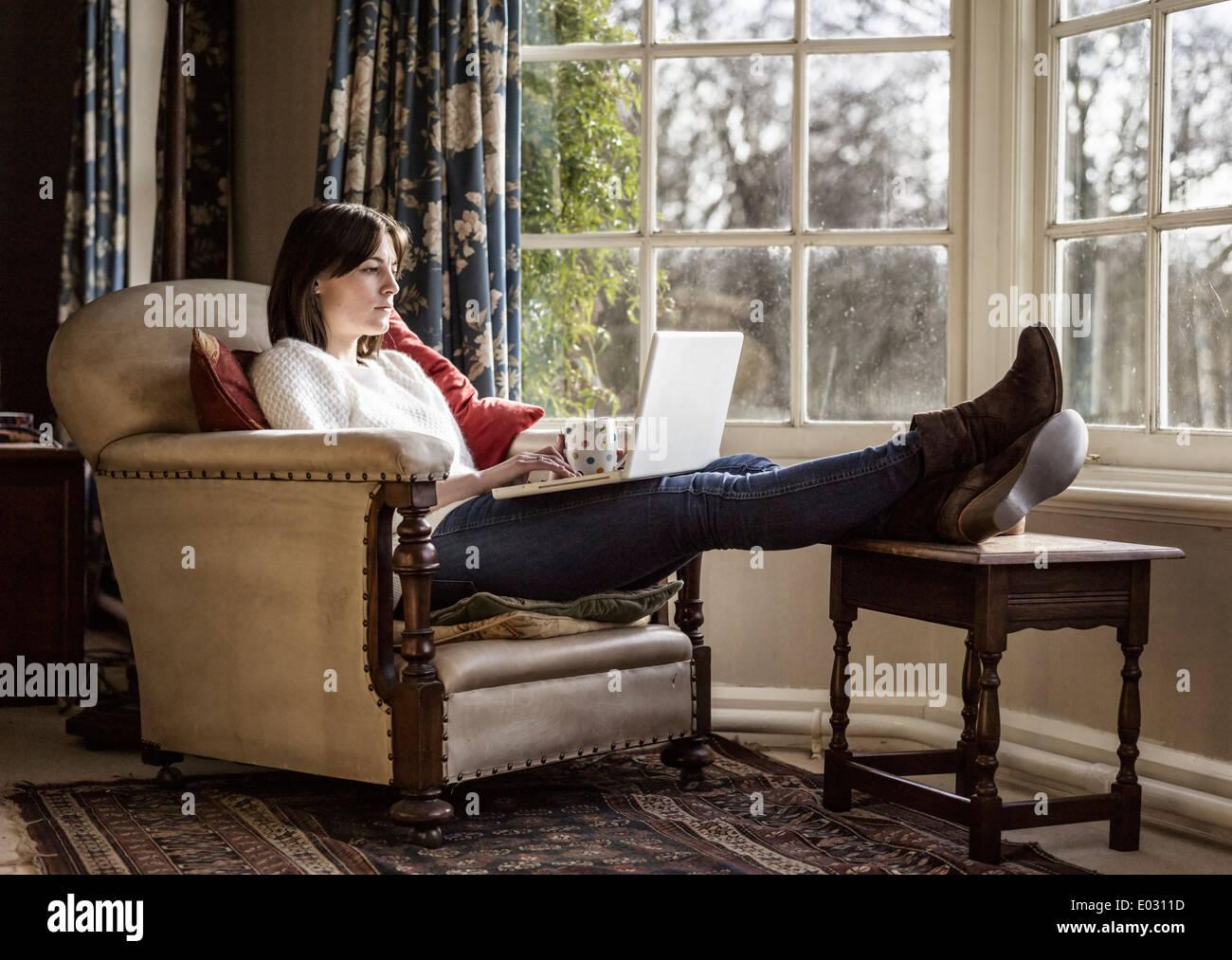 Una mujer joven para relajarse en casa con sus pies hacia arriba utilizando un ordenador portátil. Imagen De Stock