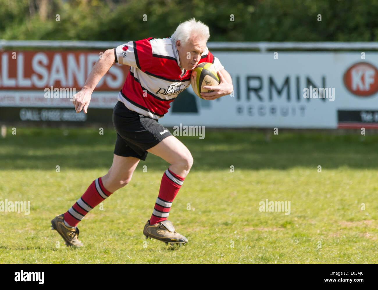 Jugador de rugby maduro corriendo con bola Imagen De Stock