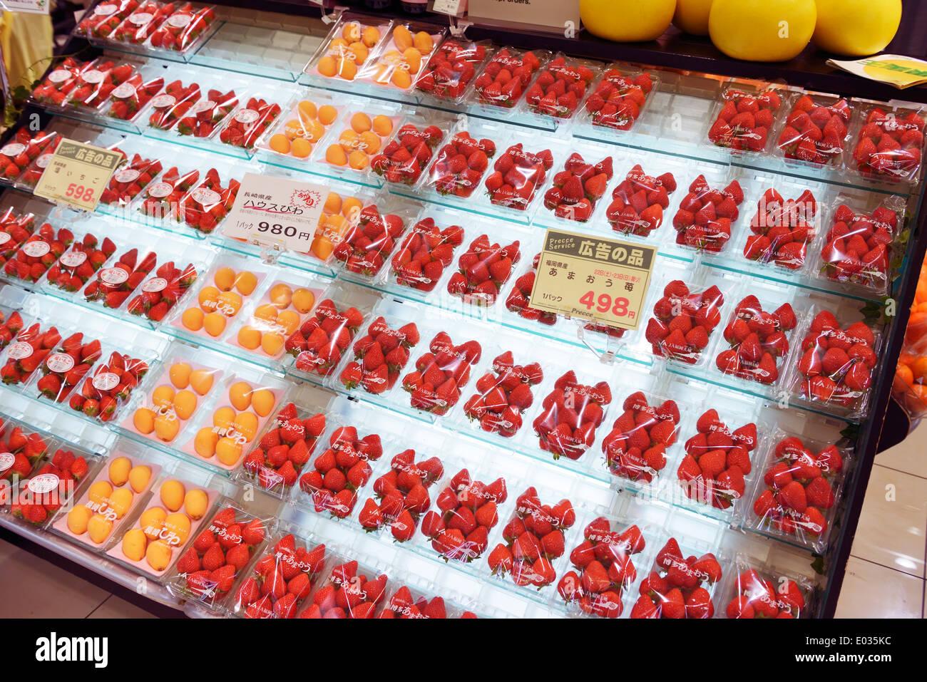 Las frutas, las fresas y el níspero en la pantalla en un supermercado japonés. Tokio, Japón. Foto de stock