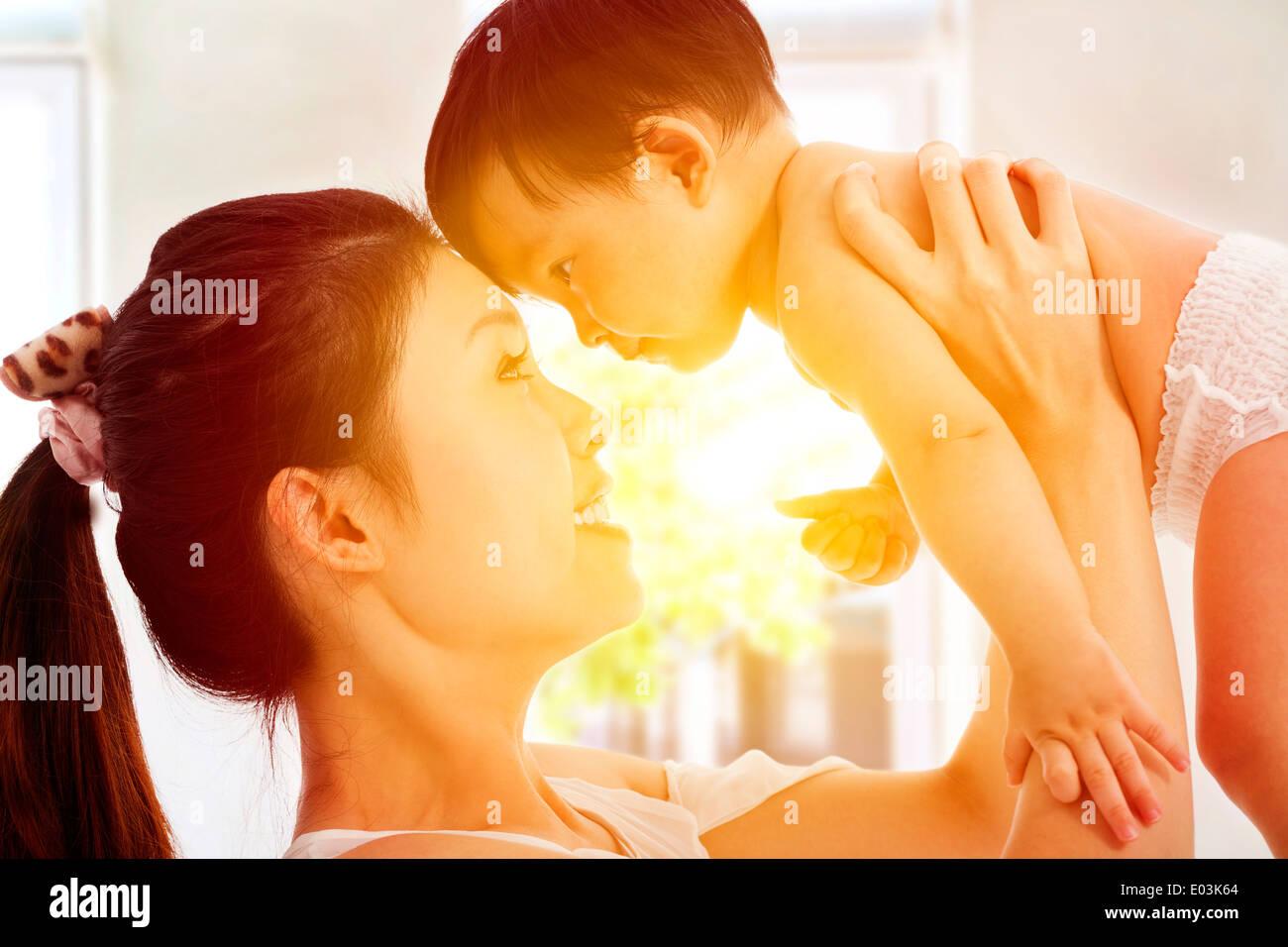 Feliz madre sosteniendo adorable bebé niño con amanecer antecedentes Foto de stock