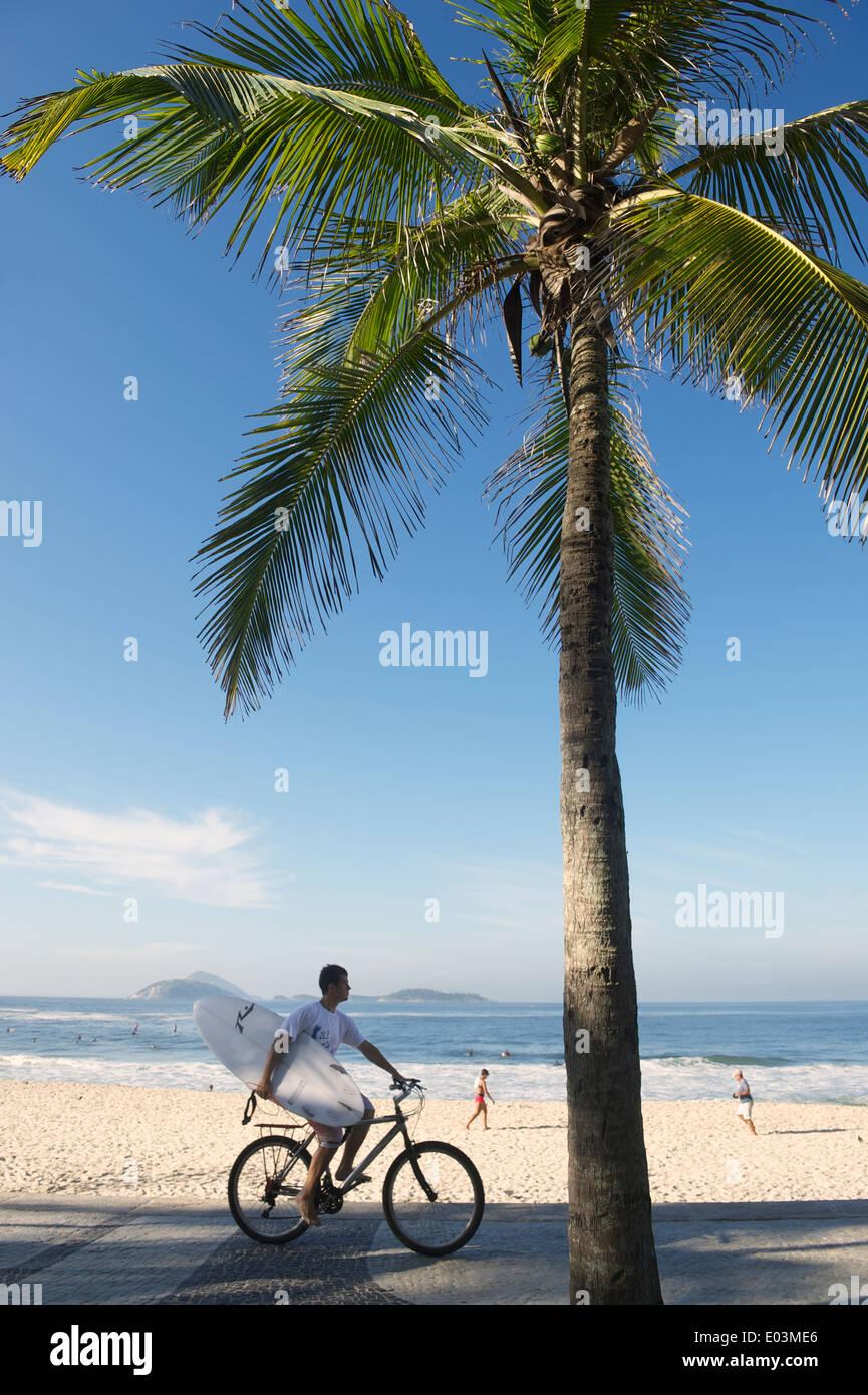 Río de Janeiro, Brasil - 21 de febrero de 2014: el hombre monta una bicicleta llevar tablas de surf a lo largo de la rambla en Arpoador junto una vista Imagen De Stock