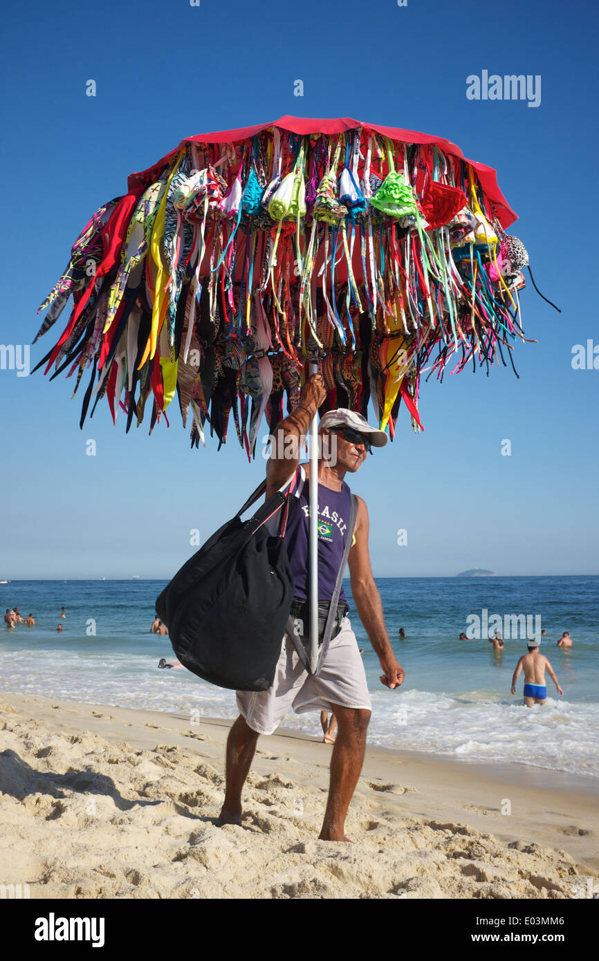 Río de Janeiro, Brasil - 22 de enero de 2014: la playa de bikinis venta proveedor lleva su mercancía a lo largo de la playa de Ipanema. Imagen De Stock