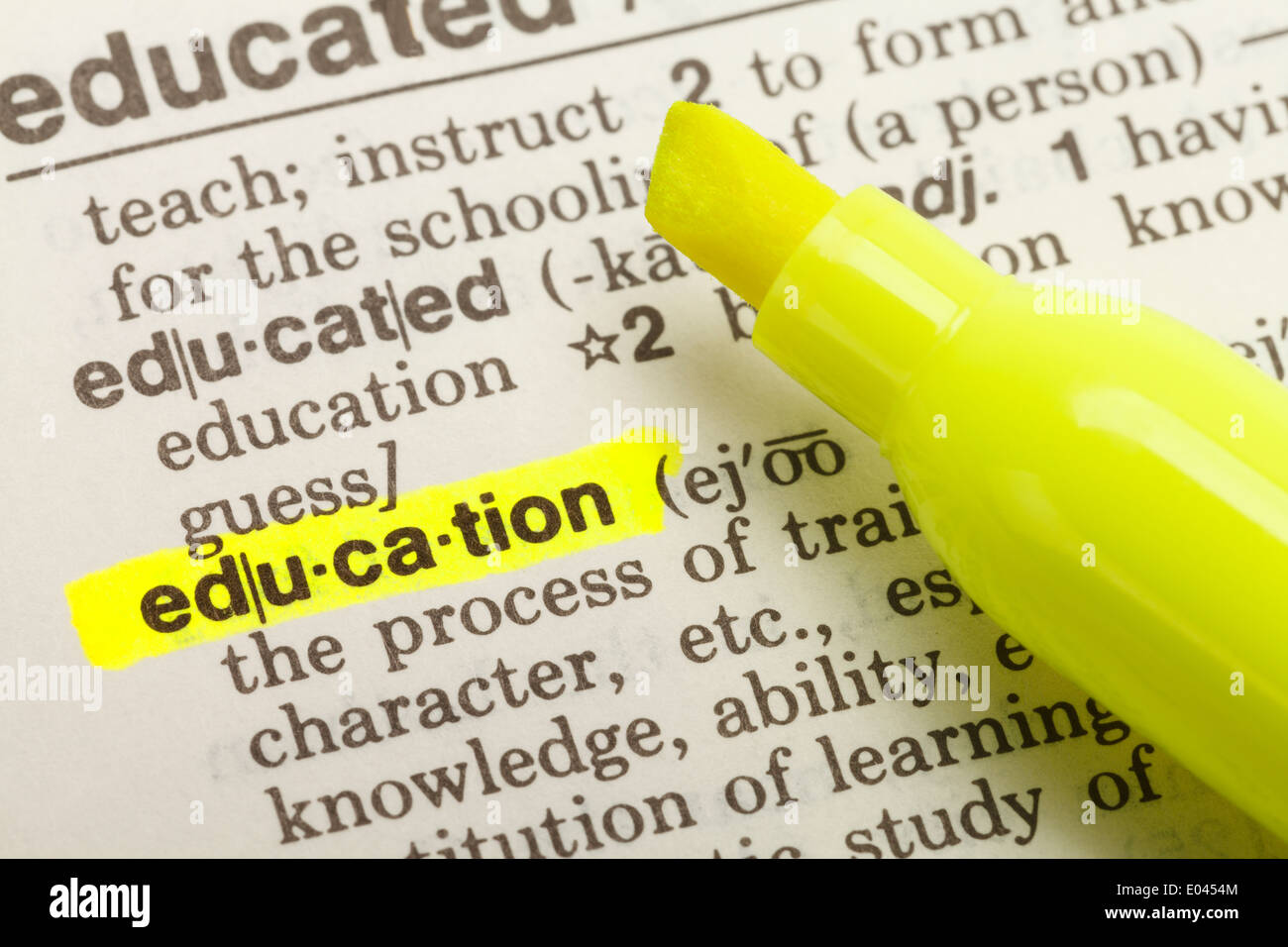 La palabra Educación subrayó en un diccionario con marcador amarillo rotulador. Imagen De Stock