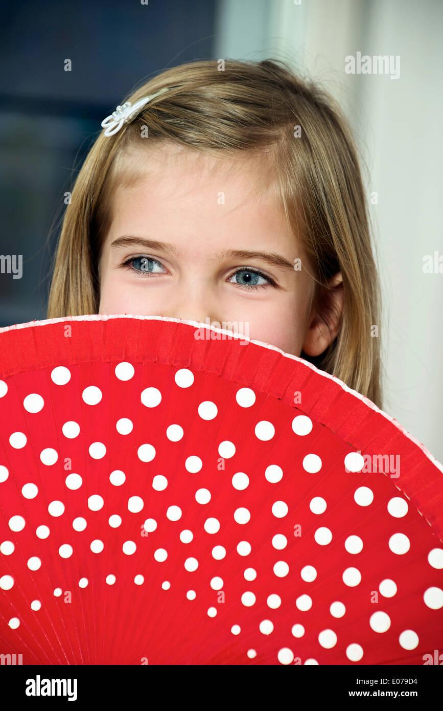 Chica sujetando abanico rojo con lunares blancos Imagen De Stock