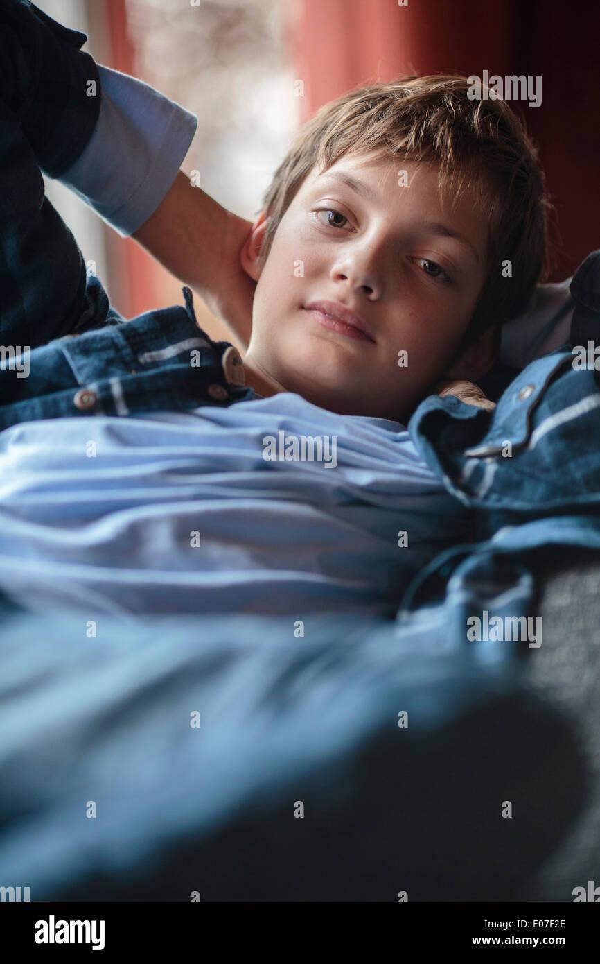 Retrato de niño reclinin, las manos detrás de la cabeza Imagen De Stock