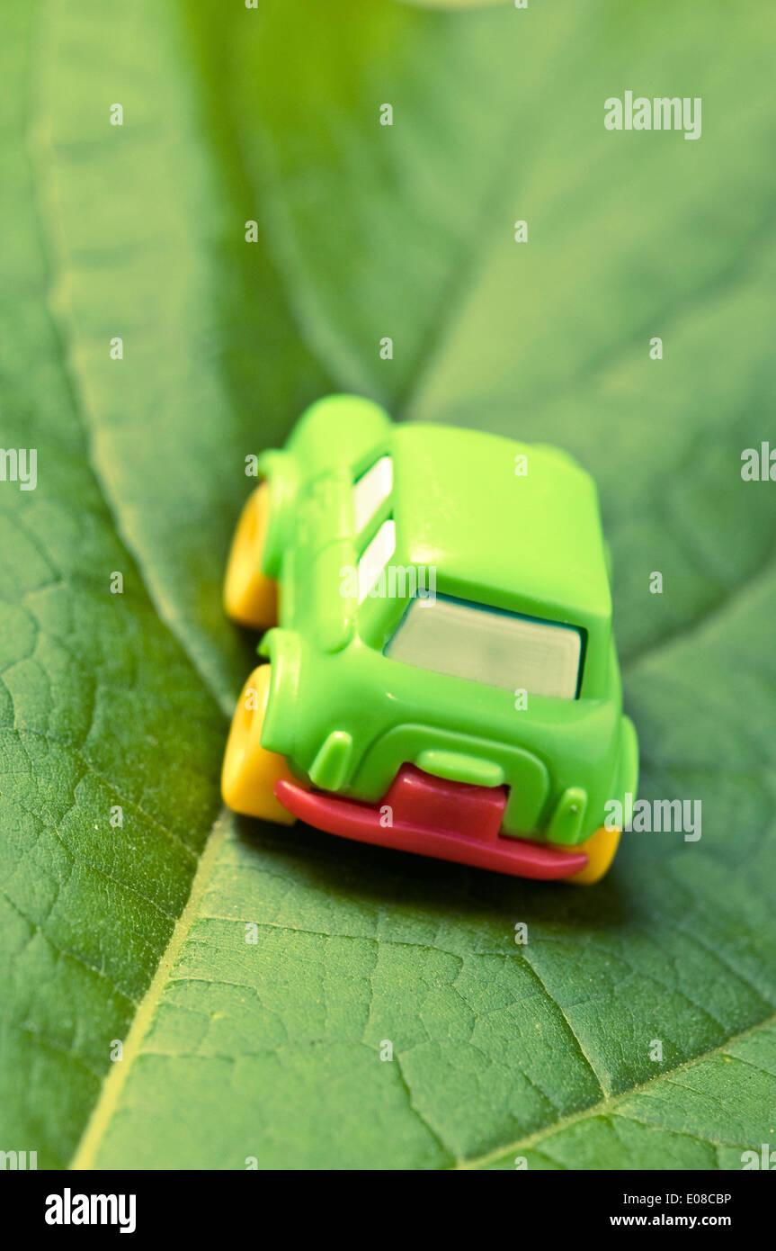 Green pequeño coche de juguete sobre una hoja verde coche concepto Imagen De Stock