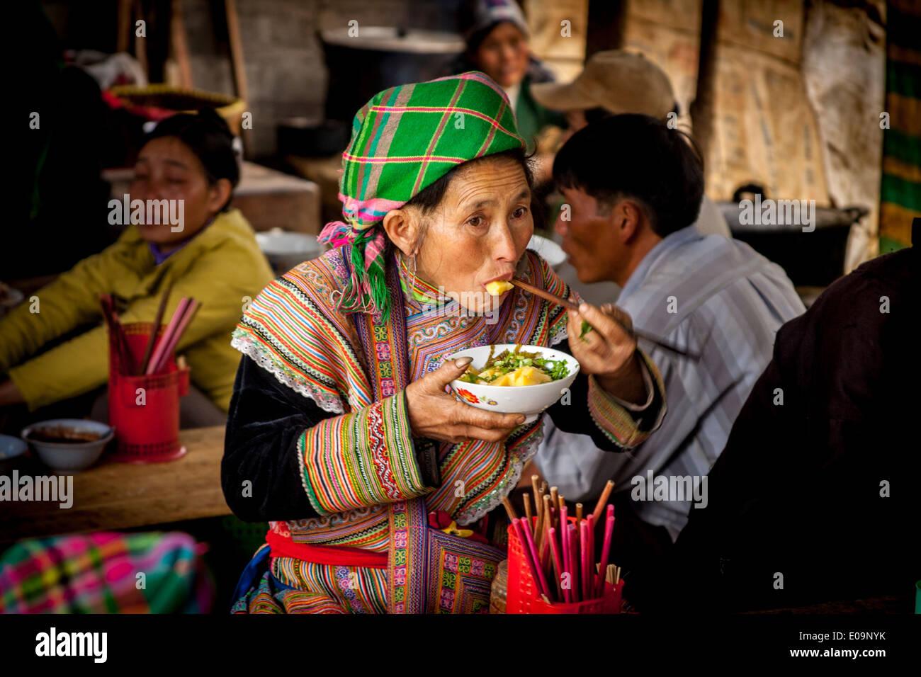 Flor Mujer Hmong comer el almuerzo en el mercado dominical de Bac Ha, provincia de Lao Cai, Vietnam Imagen De Stock