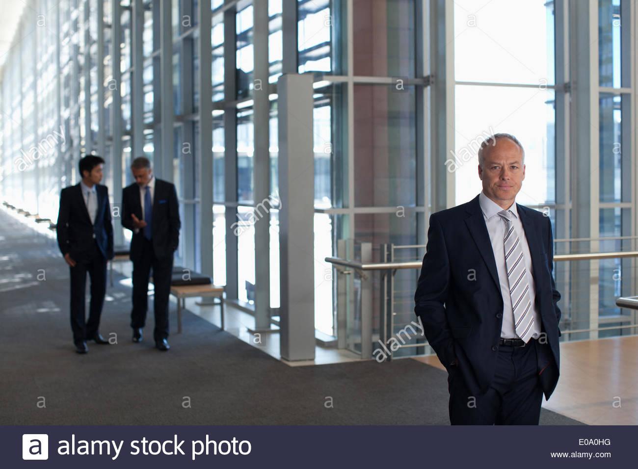 Los empresarios reunidos en ventana en la oficina vestíbulo Imagen De Stock
