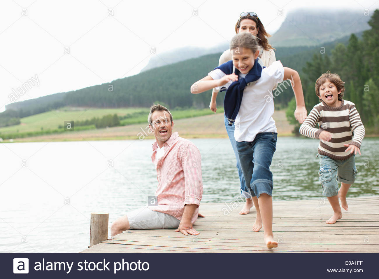 Los niños corriendo en el muelle por el lago Imagen De Stock