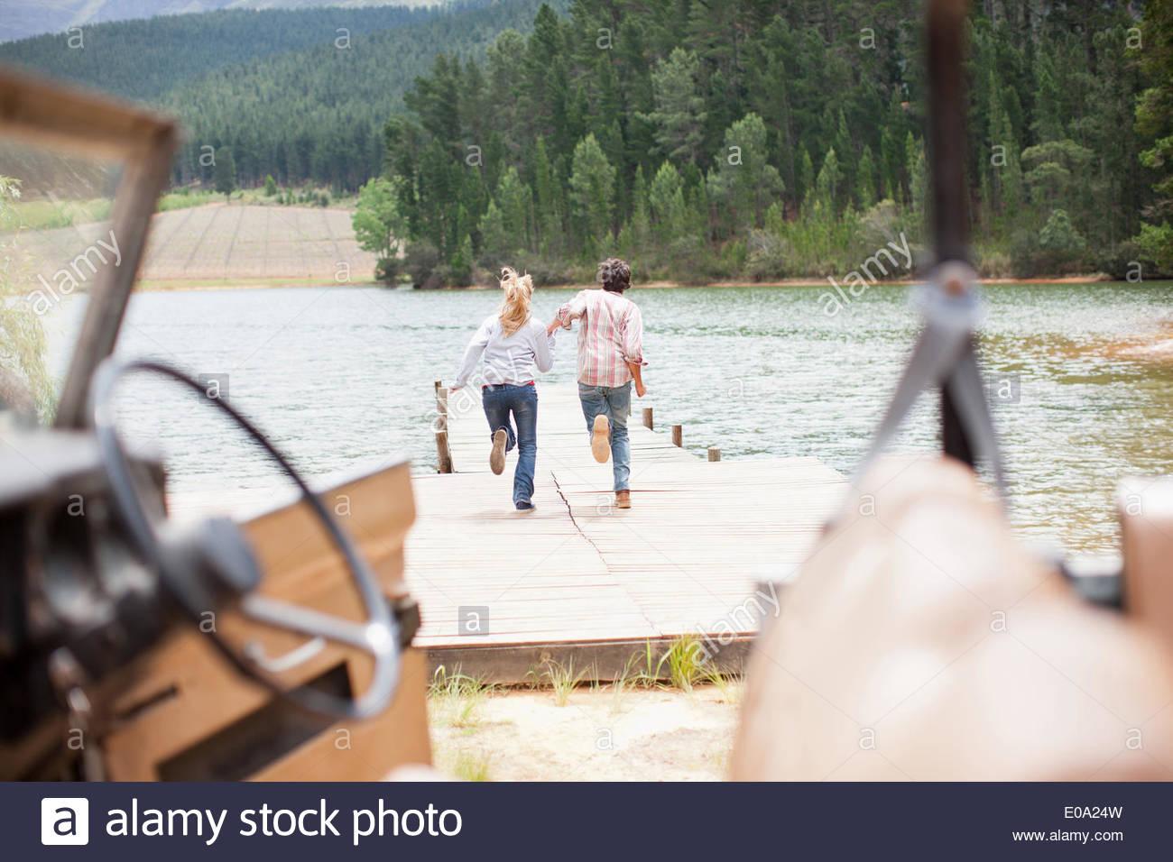 Par que corre a lo largo del muelle en el lago Imagen De Stock