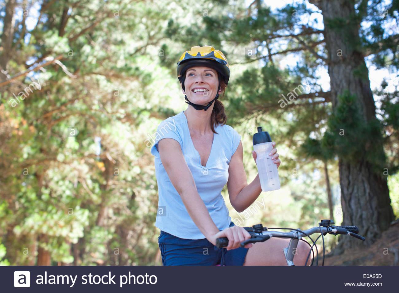 Mujer en bicicleta de agua potable en el bosque Imagen De Stock