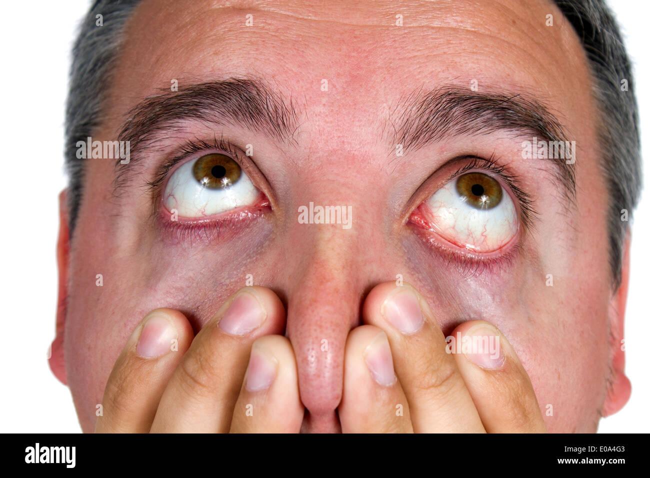 Los ojos del hombre como él mira arriba en la sorpresa y el shock. Imagen De Stock