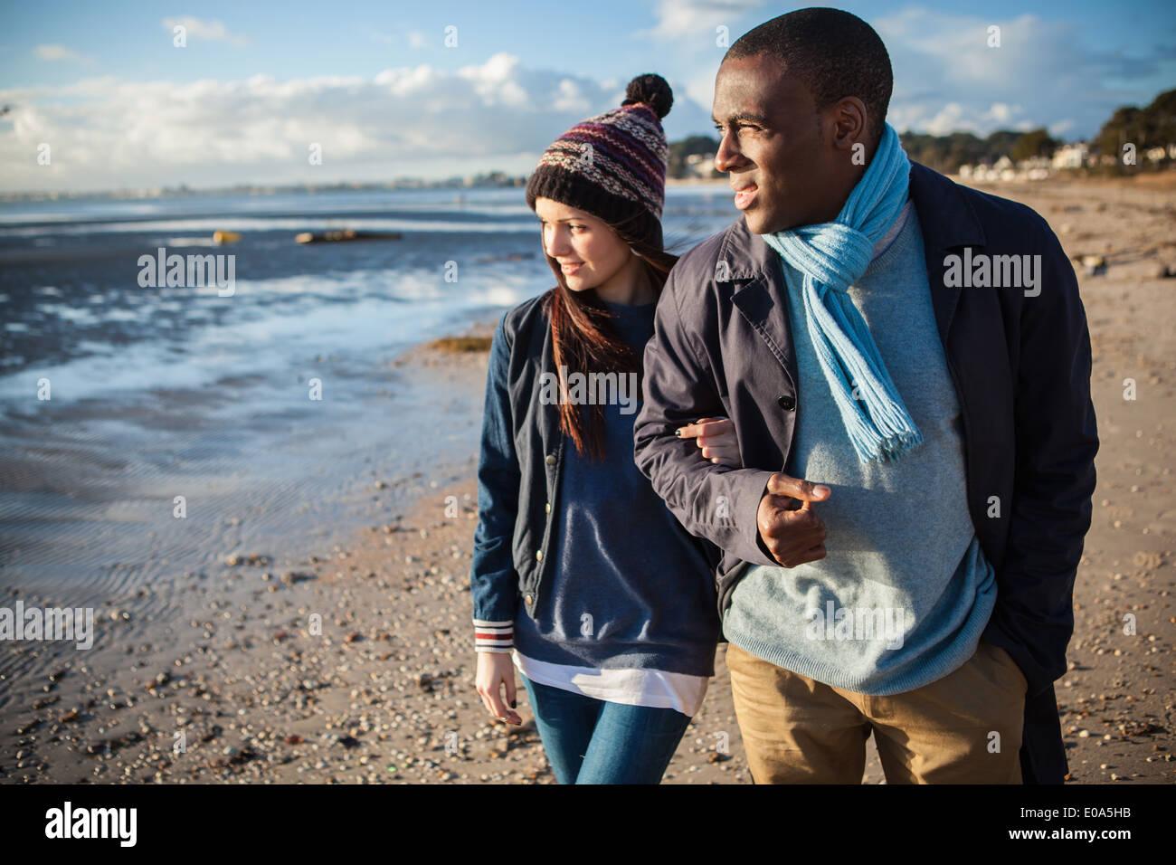 Romántica pareja joven del brazo en la playa Imagen De Stock