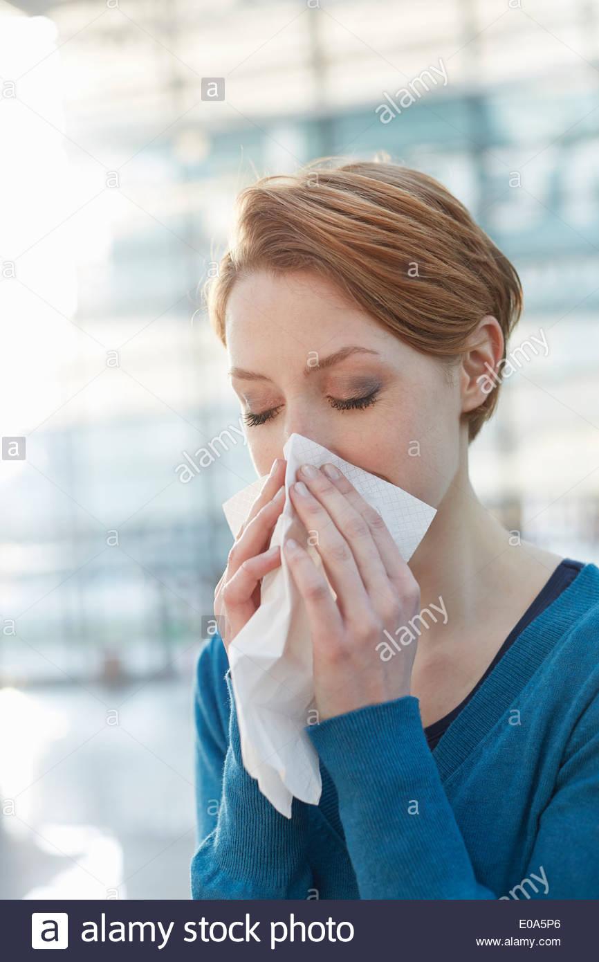 Mujer joven sonarse la nariz Imagen De Stock
