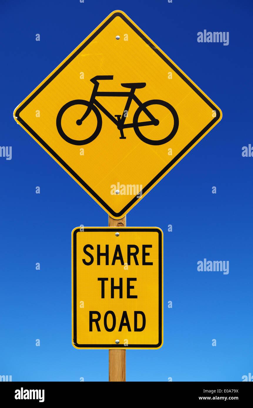 Compartir la carretera con bicicletas de carretera aislado firmar con fondo de cielo azul Imagen De Stock