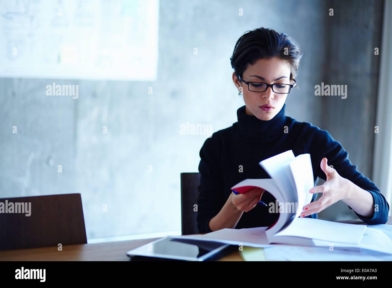 Búsqueda a través de empresarias jóvenes libro en Office Imagen De Stock