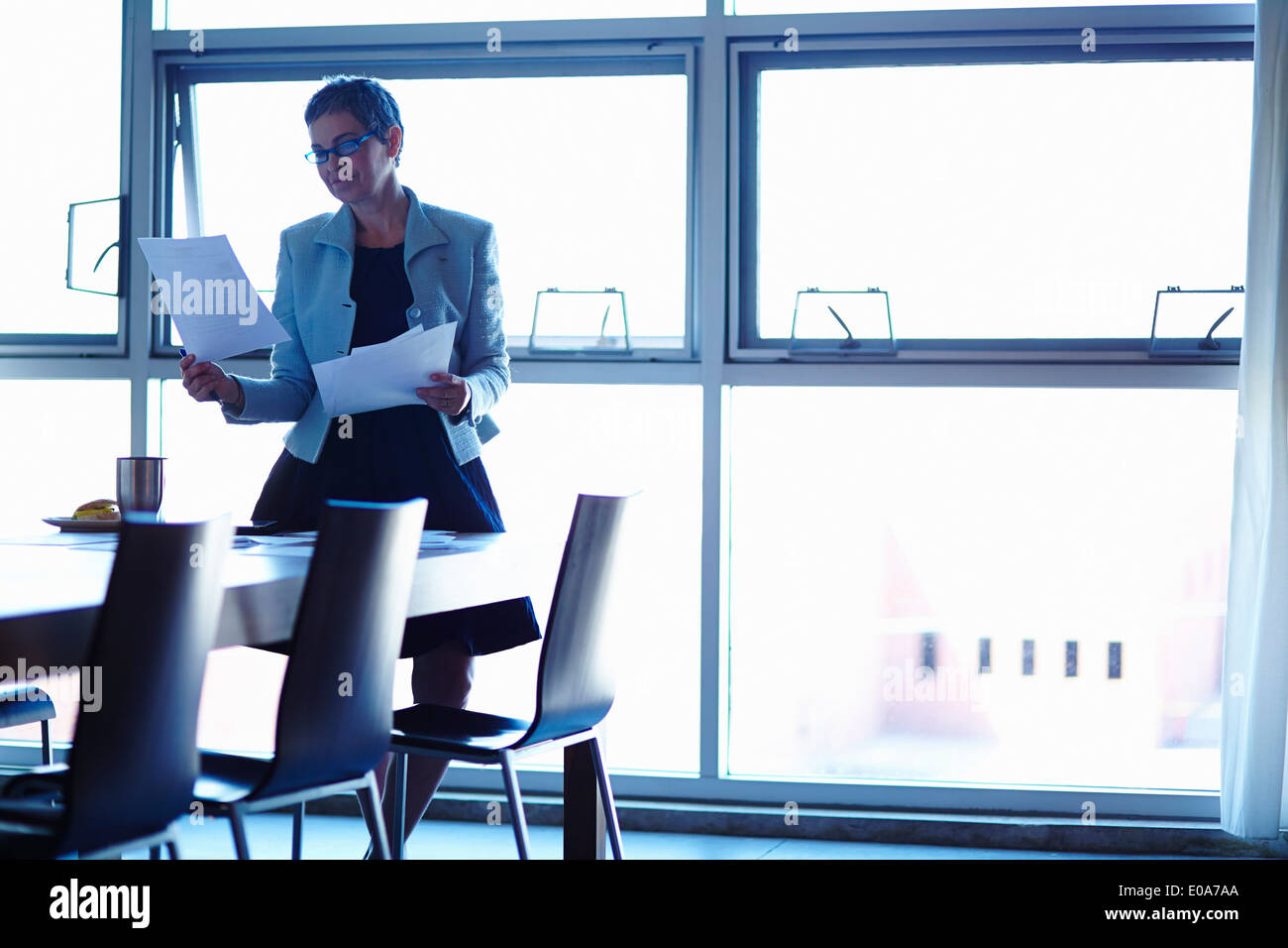 Empresaria madura en mesa de conferencia leyendo artículos Foto de stock