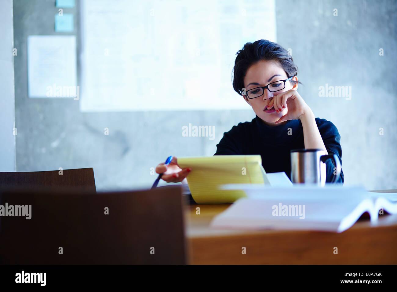 Empresarias jóvenes estudiando el papeleo en la oficina Foto de stock