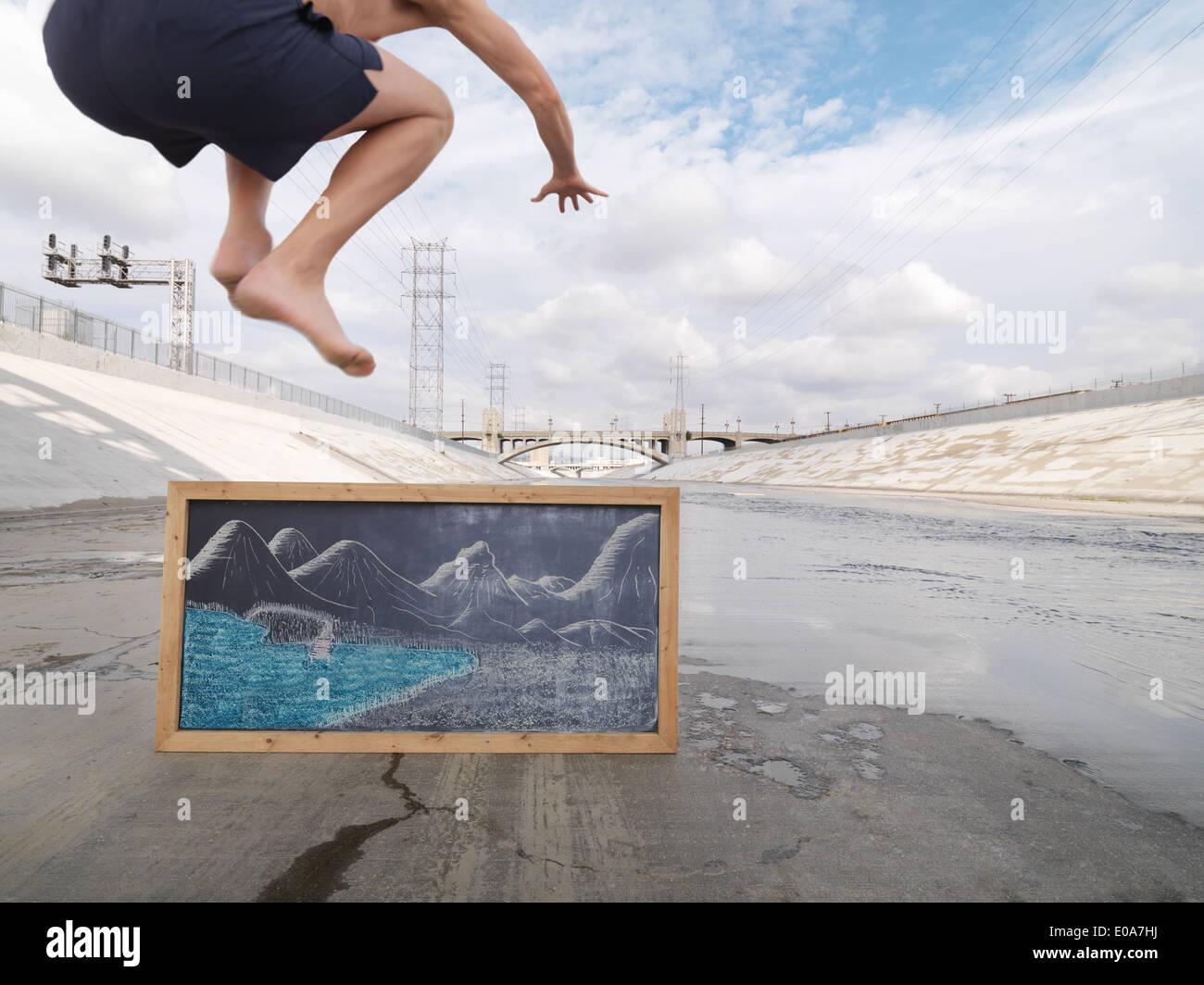 El hombre fingiendo saltar en el lago, río de Los Angeles, Los Angeles, California, EE.UU. Foto de stock