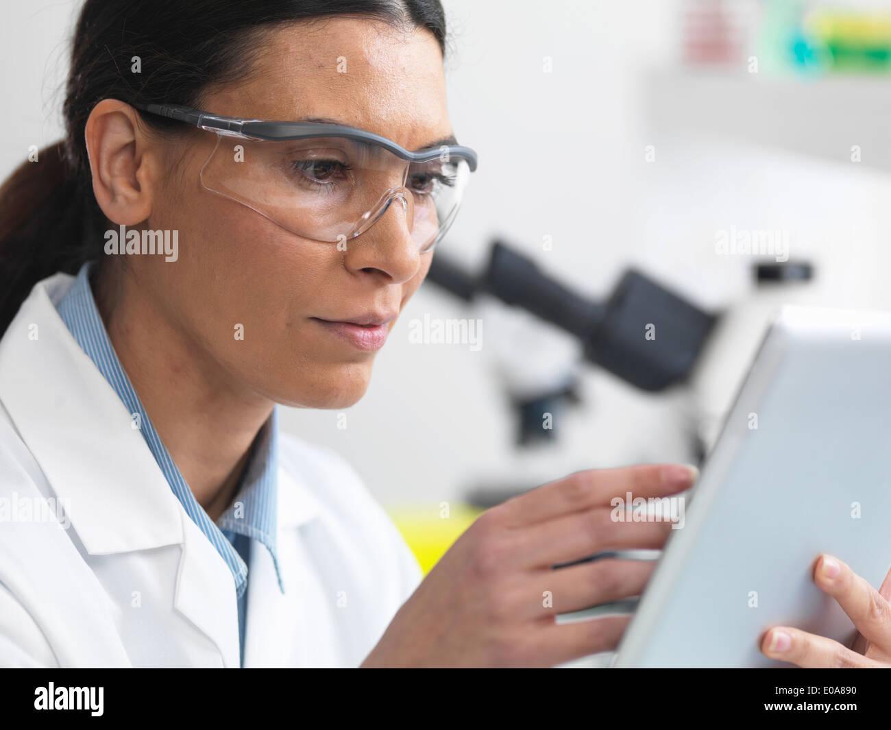 Scientist ver resultados de pruebas en una tableta digital en el laboratorio Imagen De Stock