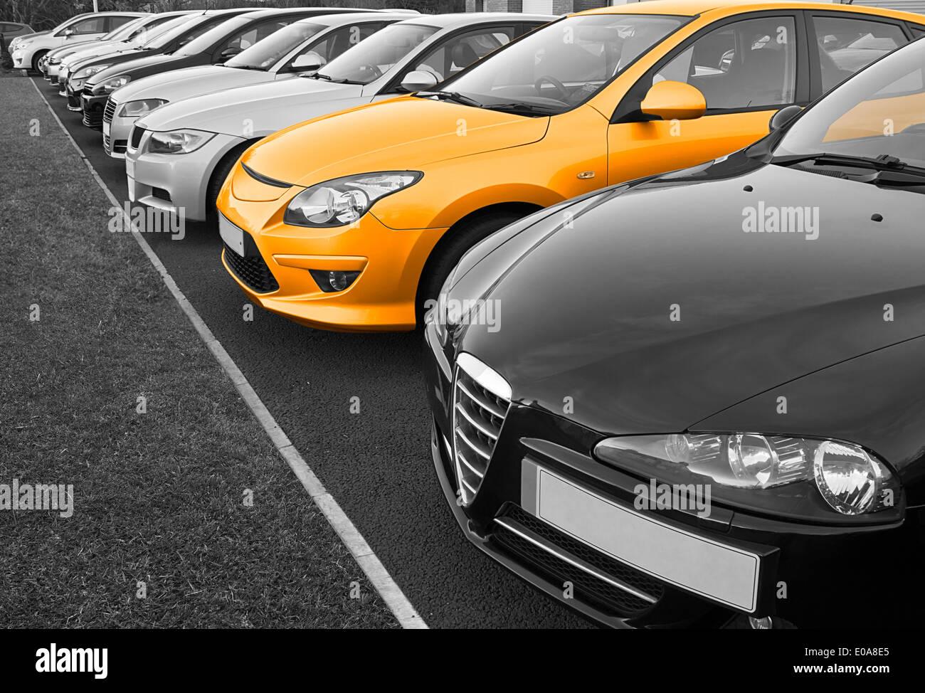 Fila de coches usados para la venta en fila con una en color, gran concepto de la elección del vehículo perfecto para comprar. Imagen De Stock