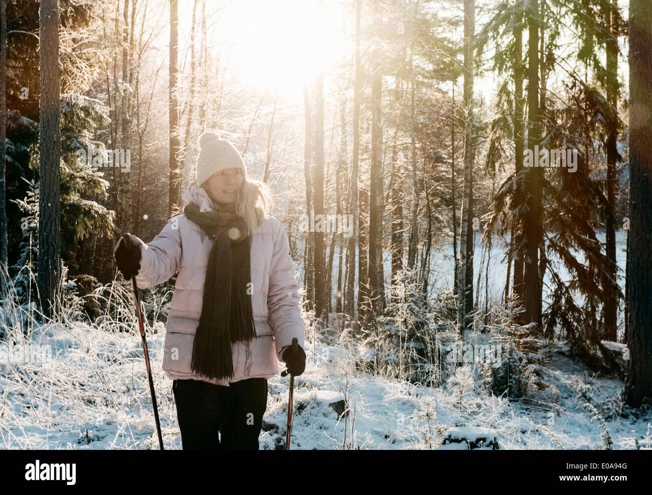 Mujer adulta media nordic walking en el bosque cubierto de nieve Imagen De Stock