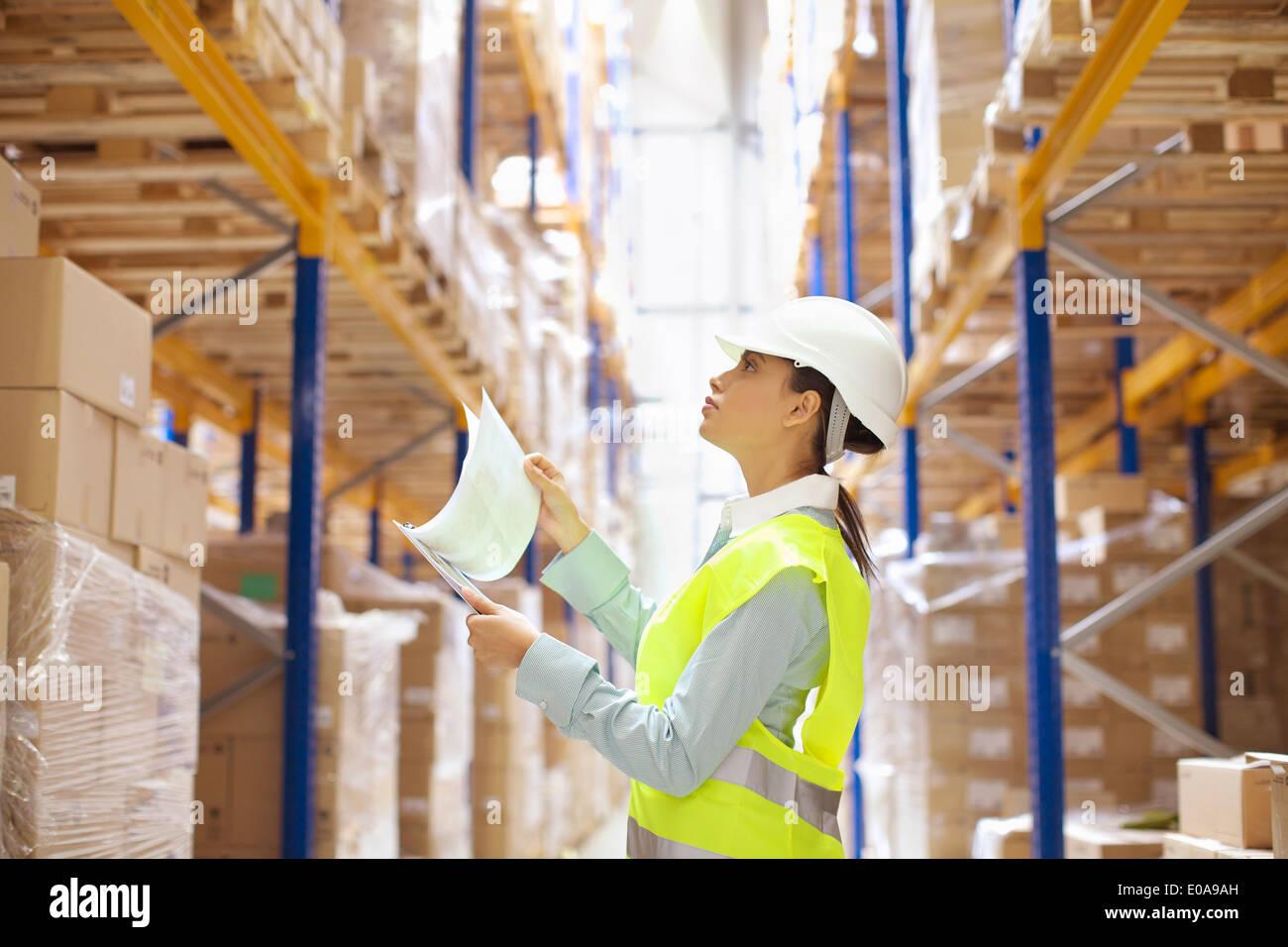 Trabajador de almacén hembra verificando acciones Imagen De Stock